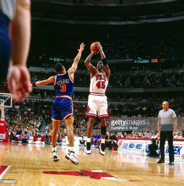 Michael Jordan of the Chicago Bulls takes a jump shot against John Starks of the New York Knicks during the NBA game at the United Center on April 16...