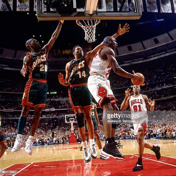 Michael Jordan of the Chicago Bulls throws a pass against Sam Perkins of the Seattle SuperSonics during Game Six of the 1996 NBA Finals at the United...