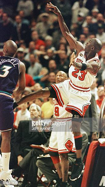 Michael Jordan of the Chicago Bulls watches his final shot as Bryon Russell of the Utah Jazz looks on 12 June during game five of the NBA Finals at...