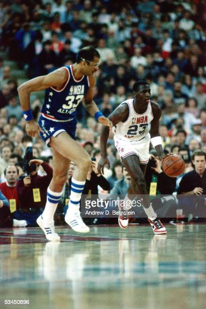 Michael Jordan of the Eastern Conference AllStars brings the ball upcourt against the Kareem AbdulJabbar of the Western Conference AllStars during...