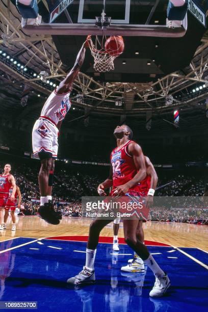Michael Jordan of the Eastern Conference AllStars dunks against Magic Johnson of the Western Conference AllStars during the 1991 NBA AllStar game on...