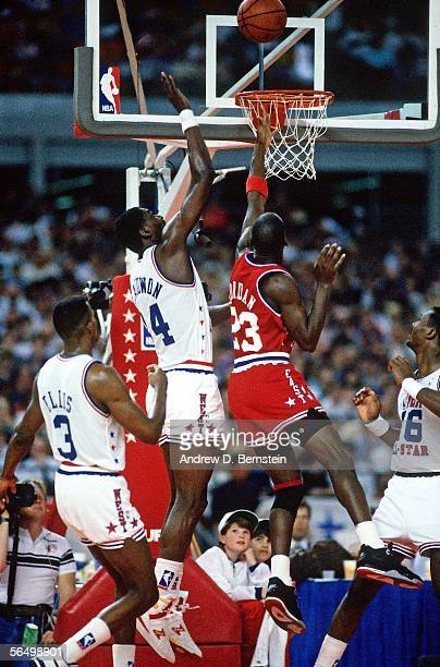 Michael Jordan of the Eastern Conference All-Stars goes for a layup over Hakeem Olajuwon of the Western Conference All-stars during the 1989 NBA...