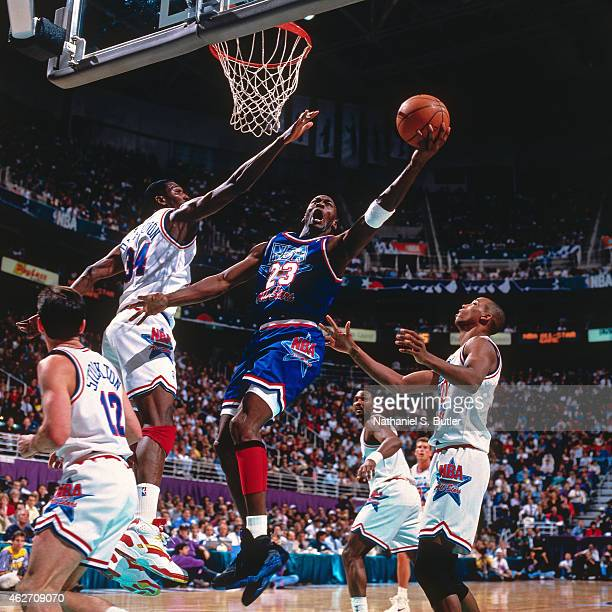 Michael Jordan of the Eastern Conference AllStars shoots against Hakeem Olajuwon of the Western Conference AllStars during the 1993 AllStar Game on...