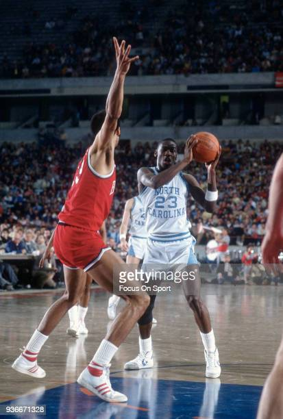 Michael Jordan of the North Carolina Tar Heels looks to pass the ball during an NCAA basketball game circa 1982 at the Greensboro Coliseum in...