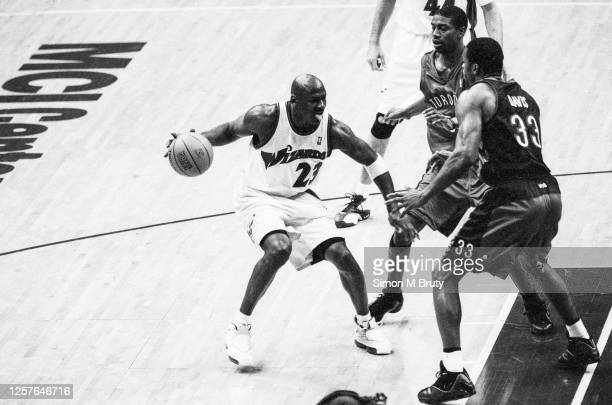 March 04: Michael Jordan of the Washington Wizards in action against Damone Brown and Antonio Davis of the Toronto Raptors at the MCI Center on March...