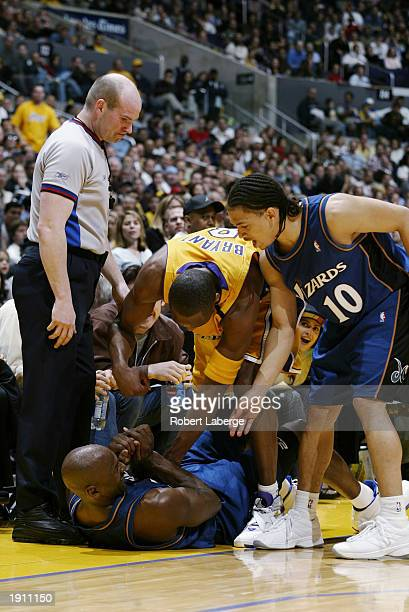 Michael Jordan of the Washington Wizards is helped up from the floor by teammate Tyronn Lue and Kobe Bryant of the Los Angeles Lakers during the game...