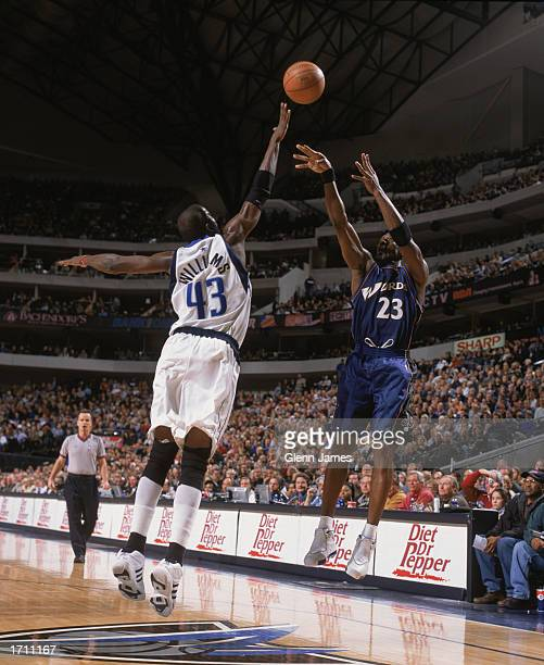 Michael Jordan of the Washington Wizards takes the jump shot over Walt Williams of the Dallas Mavericks during the game at American Airlines Center...