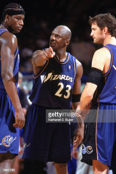 Michael Jordan of the Washington Wizards talks strategy with Kwame Brown and Christian Leattner during the game against the New York Knicks at...