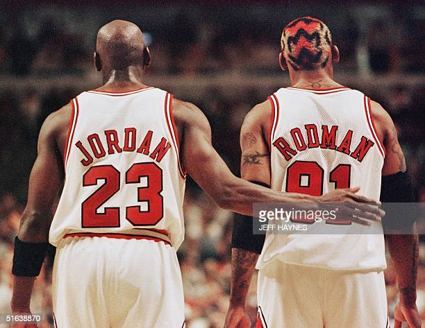 Michael Jordan pats Dennis Rodman both of the Chicago Bulls after Rodman was called for a technical foul 03 May during the second half of their NBA...