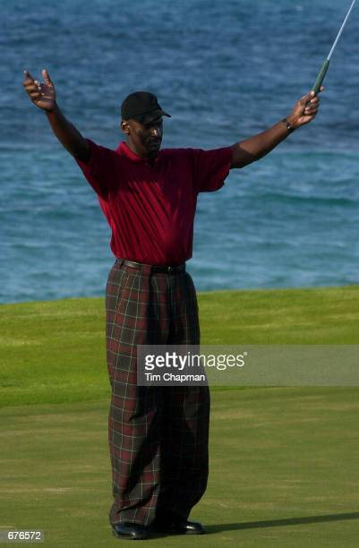 Michael Jordan raises his arms as he sinks a putt on the 17th green January 13 2001 during the Michael Jordan Celebrity Invitational at the Ocean...