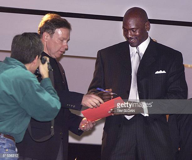 Michael Jordan signs an autograph for congressman Tom Davis while watching the Washington Wizards play the Dallas Mavericks from the owner box at MCI...