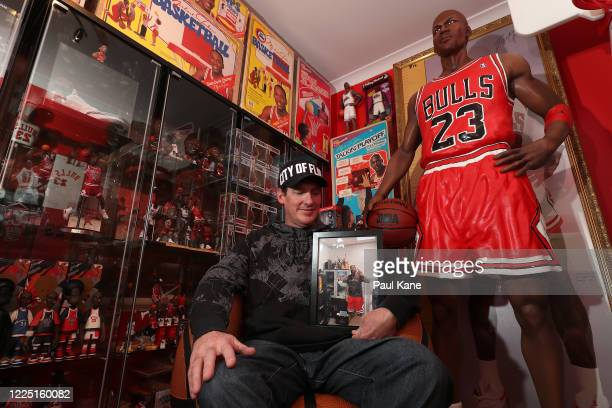 Michael Jordan toy historian Joshua De Vaney poses with a framed photograph of Marcus Jordan son of Michael who he has gifted some of his collection...