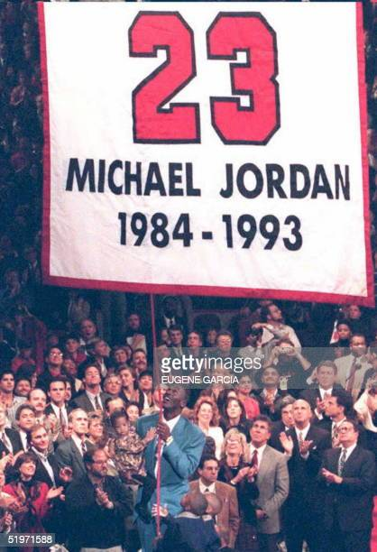 Michael Jordan who is reportedly considering returning to play professional basketball pulls a rope and raises a banner in Chicago during 01 November...