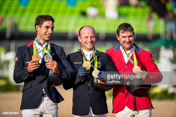 Michael Jung of Germany, Astier Nicolas of France and Phillip Dutton of the United States celebrate at the awarding ceremony of the equestrian...