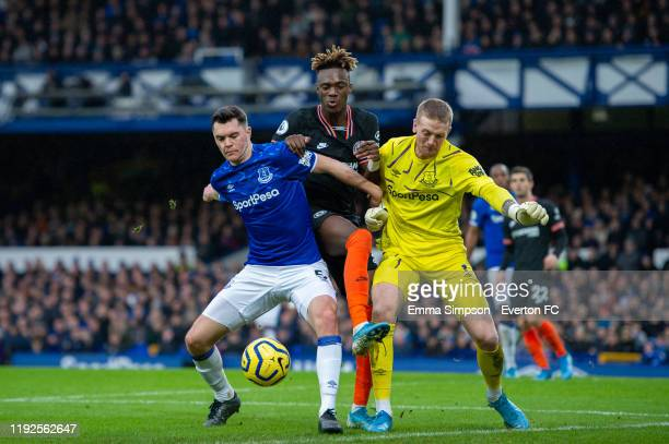 Michael Keane and Jordan Pickford of Everton attempt to shield the ball from Tammy Abraham of Chelsea during the Premier League match between Everton...