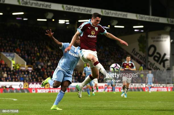 Michael Keane of Burnley clears the ball while under pressure from Saido Berahino of Stoke City during the Premier League match between Burnley and...