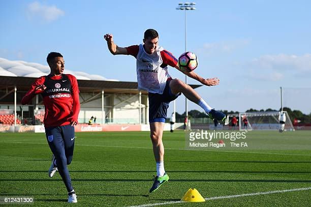 Michael Keane of England clears a ball under pressure from Jesse Lingard during an England training session at St George's Park on October 4, 2016 in...