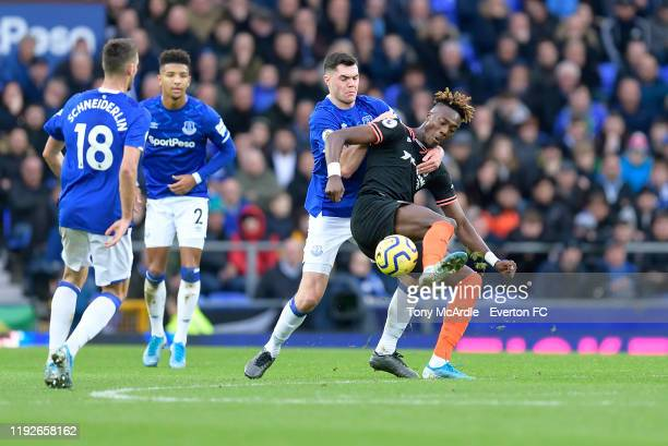 Michael Keane of Everton and Tammy Abraham challenge for the ball during the Premier League match between Everton and Chelsea at Goodison Park on...