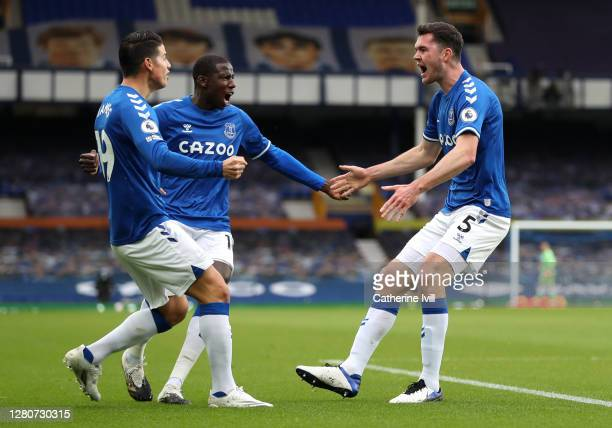 Michael Keane of Everton celebrates with teammates James Rodriguez and Abdoulaye Doucouré after scoring his sides first goal during the Premier...