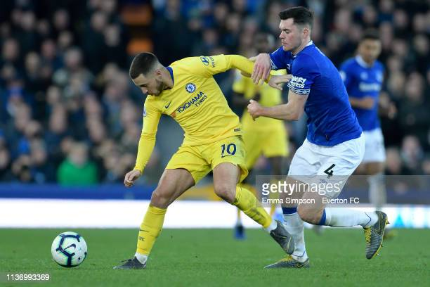 Michael Keane of Everton challenges for the ball with Eden Hazard during the Premier League match between Everton and Chelsea at Goodison Park on...
