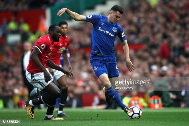 Michael Keane of Everton shoots while under pressure from Romelu Lukaku of Manchester United during the Premier League match between Manchester...