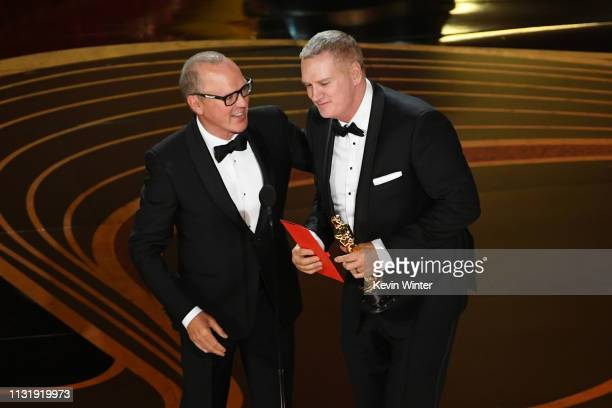 Michael Keaton presents John Ottman with the Best Film Editing award for Bohemian Rhapsody onstage during the 91st Annual Academy Awards at Dolby...