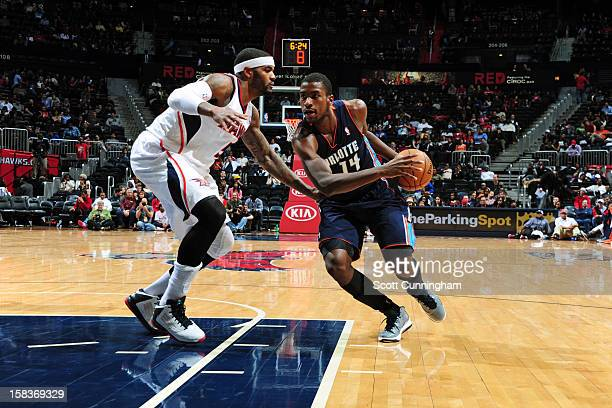 Michael KiddGilchrist of the Charlotte Bobcats handles the ball against Josh Smith of the Atlanta Hawks at Philips Arena on December 13 2012 in...