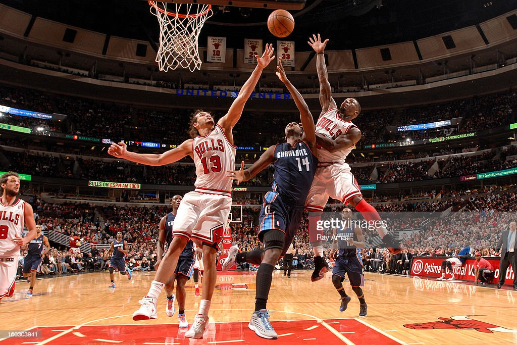Michael Kidd-Gilchrist #14 of the Charlotte Bobcats shoots a layup against Joakim Noah #13 and Nate Robinson #2 of the Chicago Bulls on January 28, 2013 at the United Center in Chicago, Illinois.