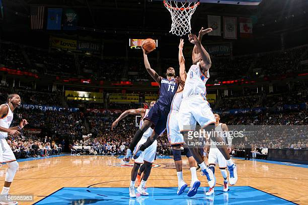 Michael KiddGilchrist of the Charlotte Bobcats shoots in the lane against Thabo Sefolosha and Serge Ibaka of the Oklahoma City Thunder on November 26...