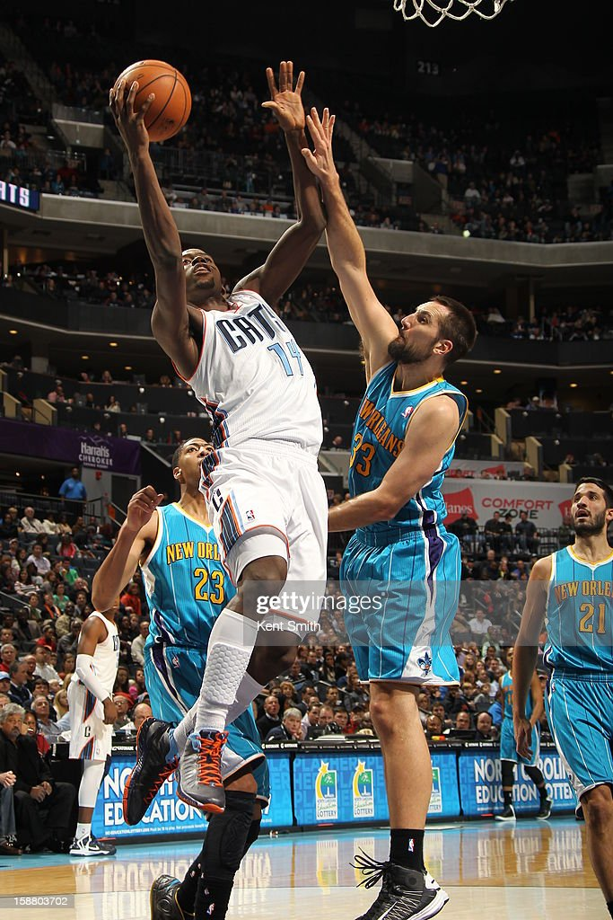 Michael Kidd-Gilchrist #14 of the Charlotte Bobcats slides to the basket against Ryan Anderson #33 of the New Orleans Hornets at the Time Warner Cable Arena on December 29, 2012 in Charlotte, North Carolina.