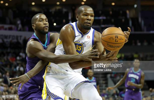 Michael KiddGilchrist of the Charlotte Hornets battles for a loose ball against Kevin Durant of the Golden State Warriors during their game at...