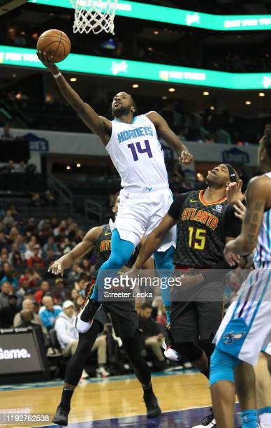 Michael KiddGilchrist of the Charlotte Hornets drives to the basket against Vince Carter of the Atlanta Hawks during their game at Spectrum Center on...
