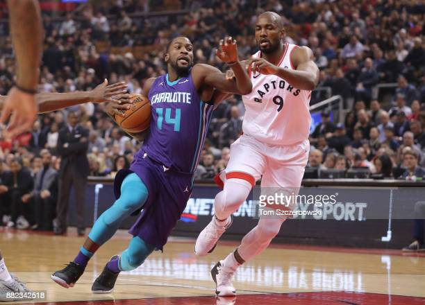 Michael KiddGilchrist of the Charlotte Hornets goes to the basket against Serge Ibaka of the Toronto Raptors during NBA game action at Air Canada...