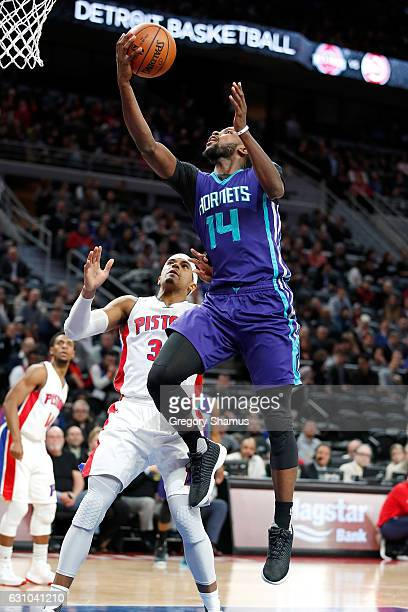 Michael KiddGilchrist of the Charlotte Hornets tries to get a shot off past Tobias Harris of the Detroit Pistons during the first half at the Palace...