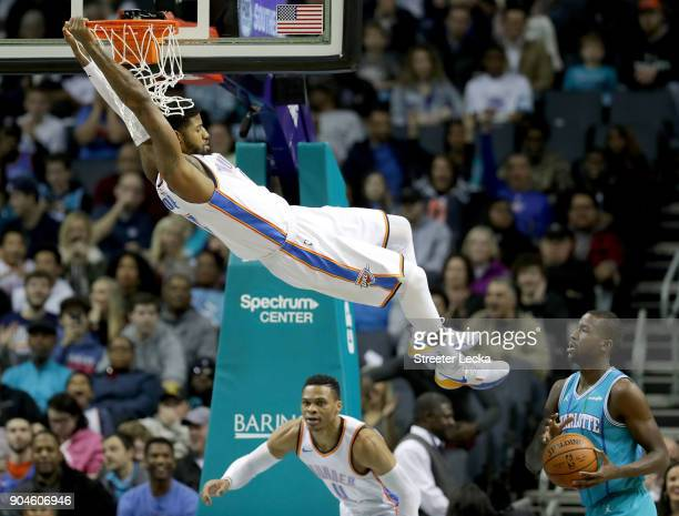 Michael KiddGilchrist of the Charlotte Hornets watches as Paul George of the Oklahoma City Thunder swings from the rim after a dunk during their game...