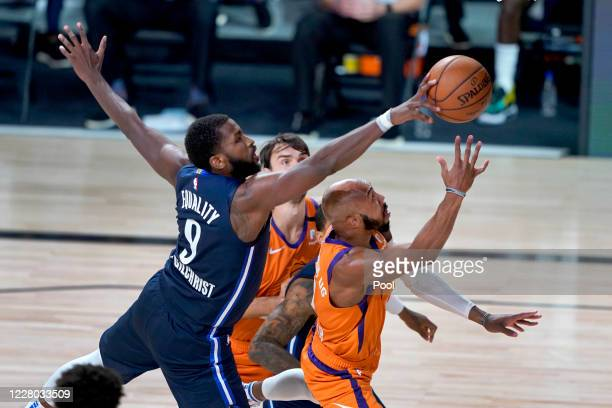 Michael Kidd-Gilchrist of the Dallas Mavericks knocks the ball away from Jevon Carter of the Phoenix Suns during the second half at AdventHealth...