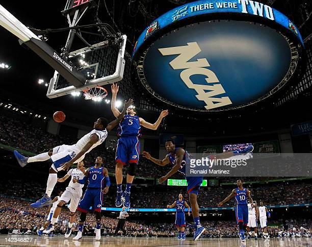 Michael KiddGilchrist of the Kentucky Wildcats is fouled as he goes to the basket against Elijah Johnson and Jeff Withey of the Kansas Jayhawks in...