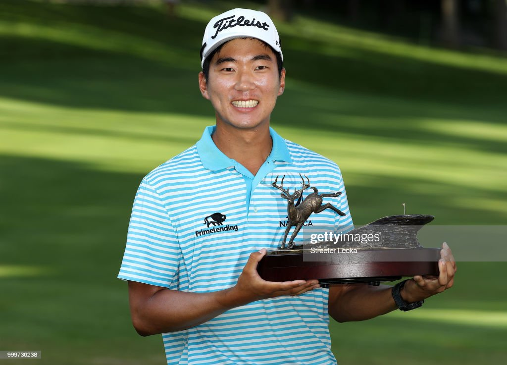 Michael Kim celebrates with the trophy after winning the John Deere Classic during the final round at TPC Deere Run on July 15, 2018 in Silvis, Illinois.