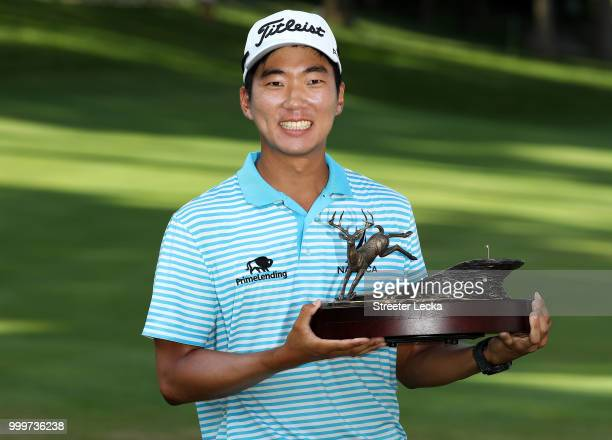 Michael Kim celebrates with the trophy after winning the John Deere Classic during the final round at TPC Deere Run on July 15 2018 in Silvis Illinois