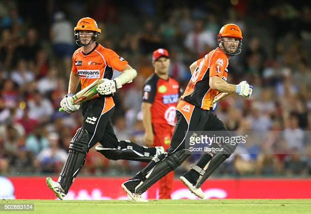 Michael Klinger and Shaun Marsh of the Scorchers run between the wickets as Aaron Finch captain of the Renegades looks on during the Big Bash League...