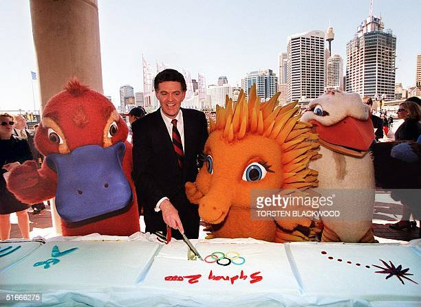"""Michael Knight , Minister for the Olympics, cuts a portion of the world's longest Olympic cake with Sydney 2000 mascots """"Syd"""" the platypus , """"Millie""""..."""