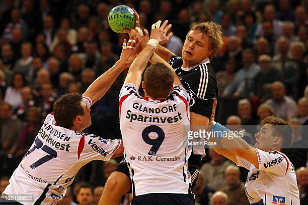 Michael Knudsen and Holger Glandorf of FlensburgHandewitt are challenged by Aron Palmarsson of Kiel during the Toyota HBL match between SG...