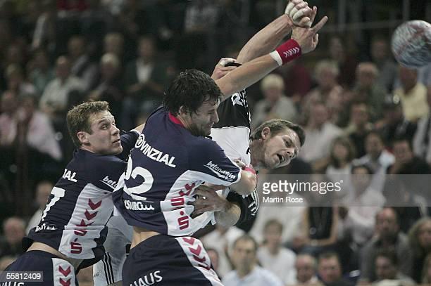 Michael Knudsen and Marcin Lijewski attacks Frode Hagen of Kiel during the German Handball Federation Cup match between THW Kiel and SG Flensburg...