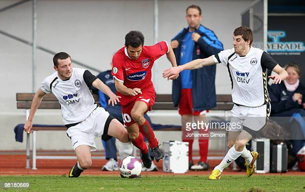 Michael Kokocinski and Christian Brucia of Burghausen in action with Alper Bagceci of Heidenheim, watched by Andreas Spann of Heidenheim during the...