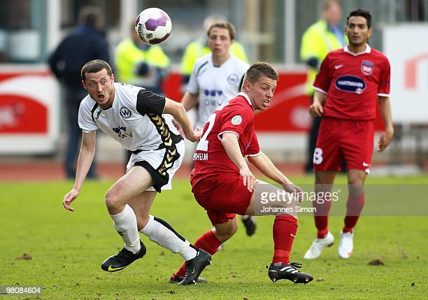 Michael Kokocinski of Burghausen battles for the ball with Bastian Heidenfelder of Heidenheim during the third division match between Wacker...