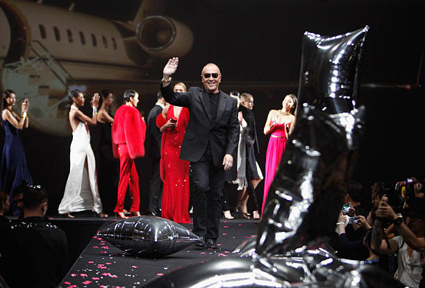 e2587312667 Michael Kors waves to guests after The Michael Kors Jet Set Experience  fashion show on May