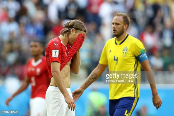 Michael Lang of Switzerland walks off the pitch after recieving a red card during the 2018 FIFA World Cup Russia Round of 16 match between Sweden and...
