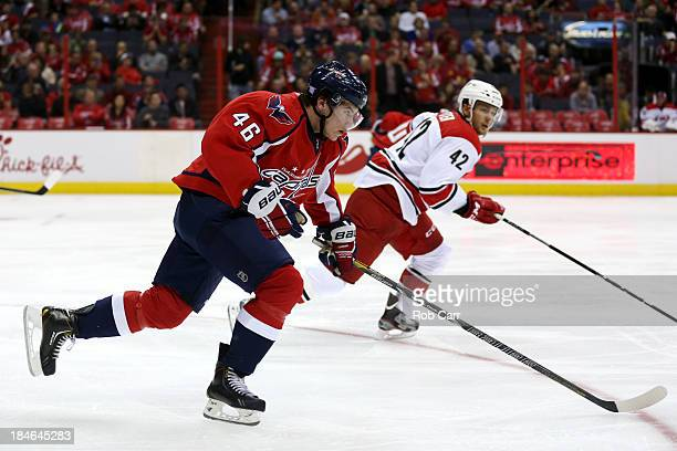 Michael Latta of the Washington Capitals and Brett Sutter of the Carolina Hurricanes go after the puck at Verizon Center on October 10, 2013 in...