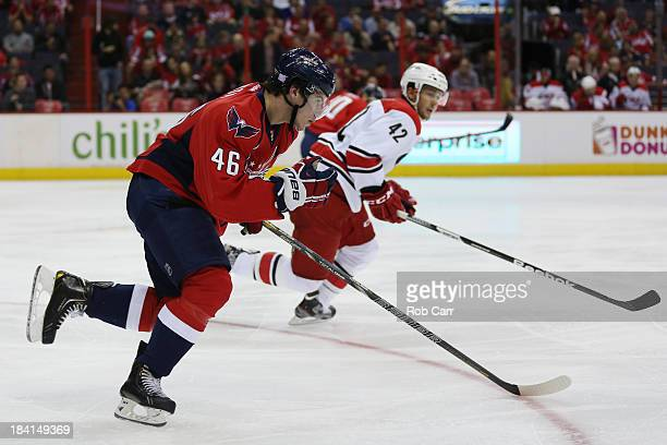 Michael Latta of the Washington Capitals and Brett Sutter of the Carolina Hurricanes skate after the puck at Verizon Center on October 10, 2013 in...