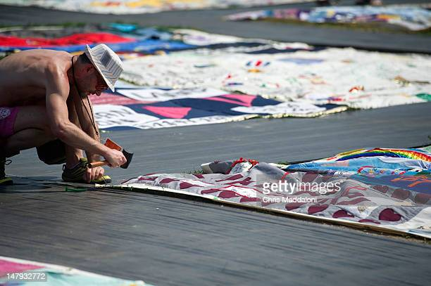 Michael Ledford an HIV positive volunteer from Washington DC helps maintain the AIDS Memorial Quilt at the annual Smithsonian Folklife Festival on...